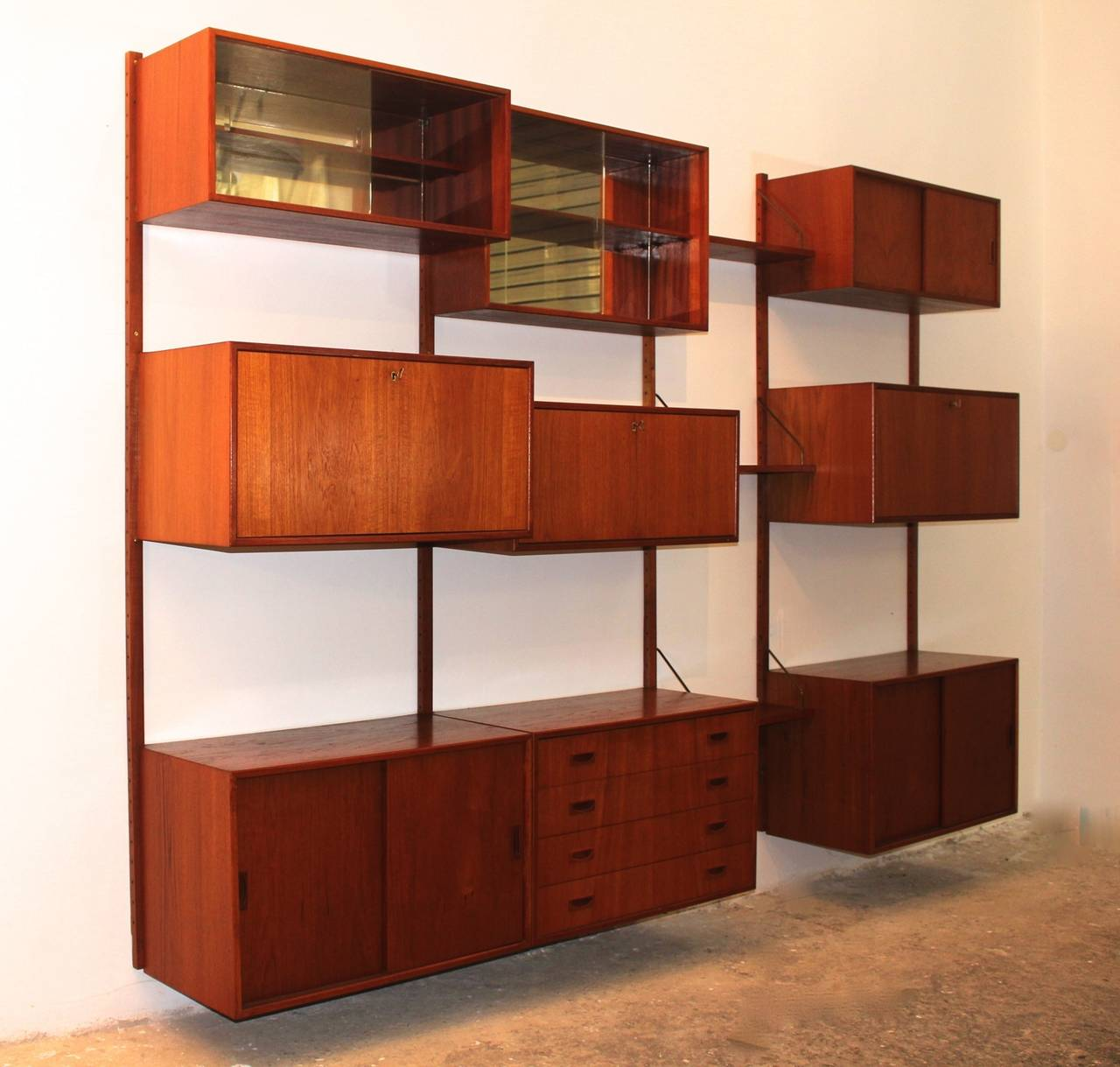 A Scandinavian Modern teak vintage wall system or shelves unit by Poul Cadovius, which features drawer chest, writing flap and storage chest with sliding doors.