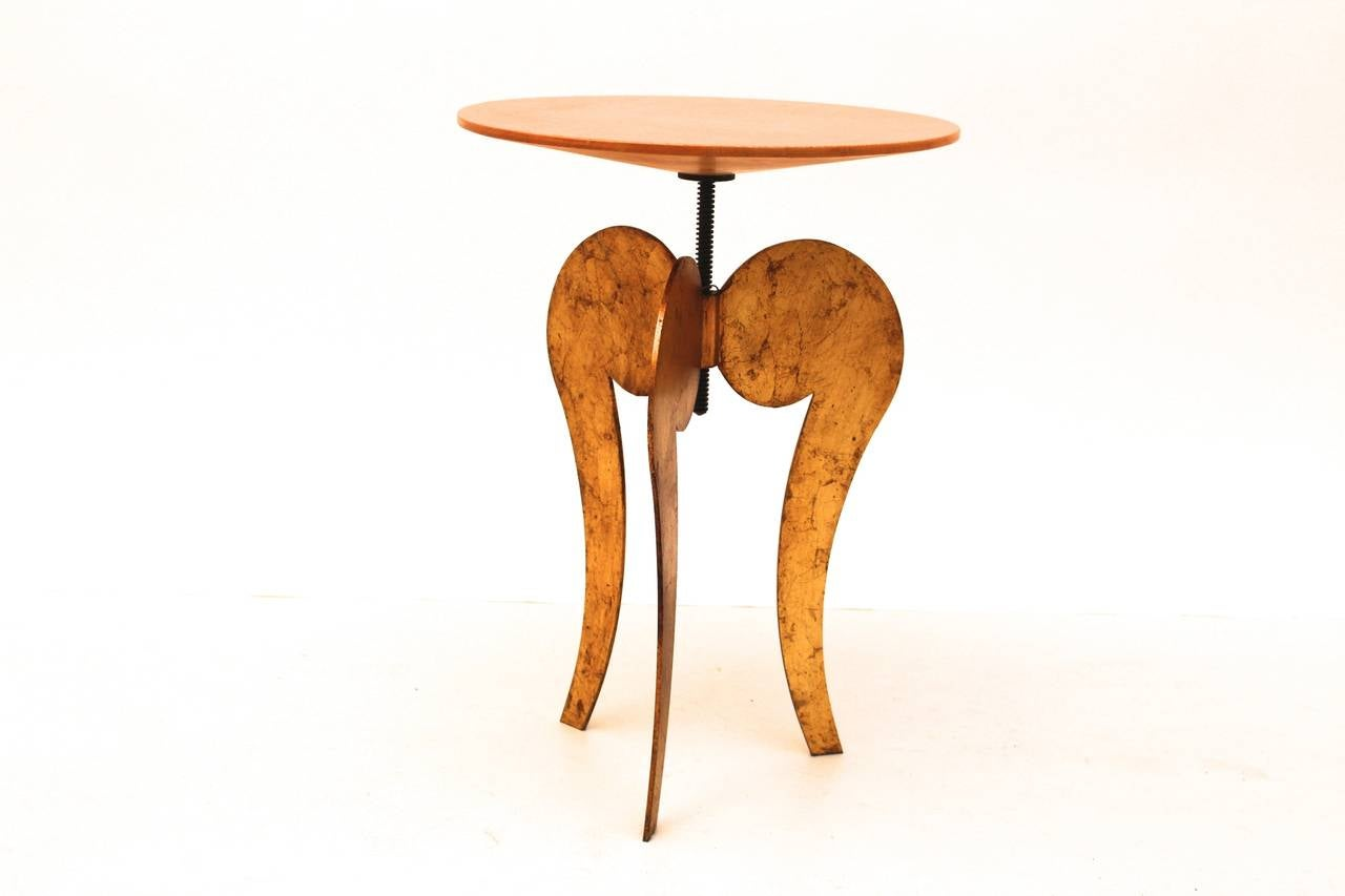 The base is made of steel gilded with a wooden top and is adjustable from 19.69 in. to 22.83 in.  This Side Table was designed by Sergio Terzani and Jean Francais Crochet and Scandicci, 1985.