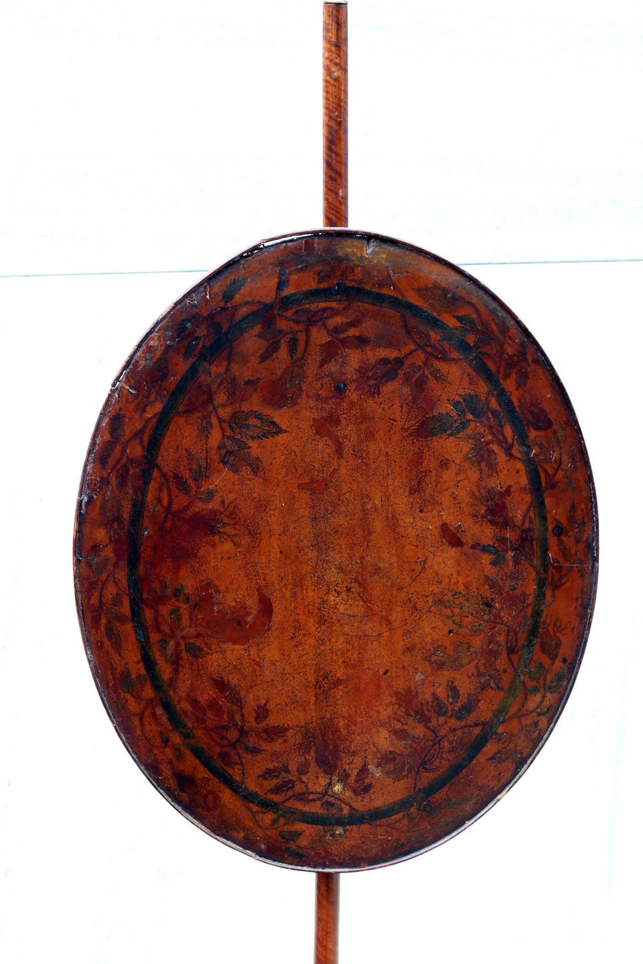 Mahogany and maple pole screen on a tripod base featuring a center urn, adjustable brass slide and a lead weighted bottom. Stenciled floral motif on screen. Exceptional all-original finish, circa 1800. See measurements below.