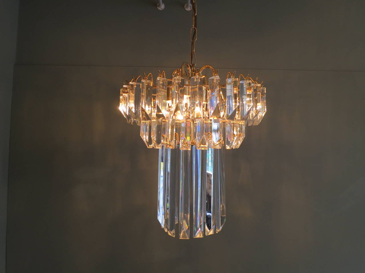 An unusual shaped chandelier in Murano crystal, with 3 tiers 2 short and 1 long. On a gold lacquered frame with four light fittings.  Drop with chain 97cm