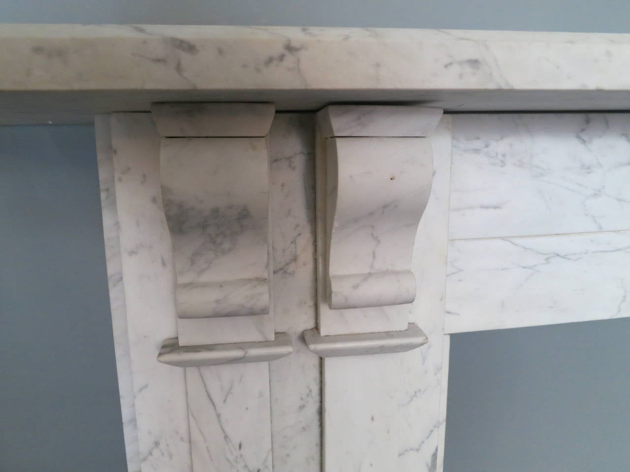 A large and imposing English William IV fireplace in pencil vein Carrara marble, with paneled pilaster jambs with twin corbel brackets supporting a long wide and generous mantel. Some minor restorations.