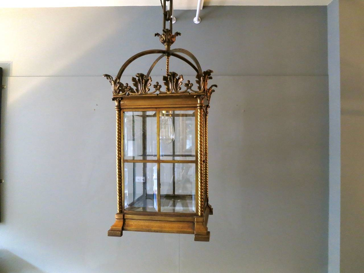 A 19th century period lantern in gilt brass, with Corinthian columns supporting an acanthus leaf decoration and bevelled glass panels.