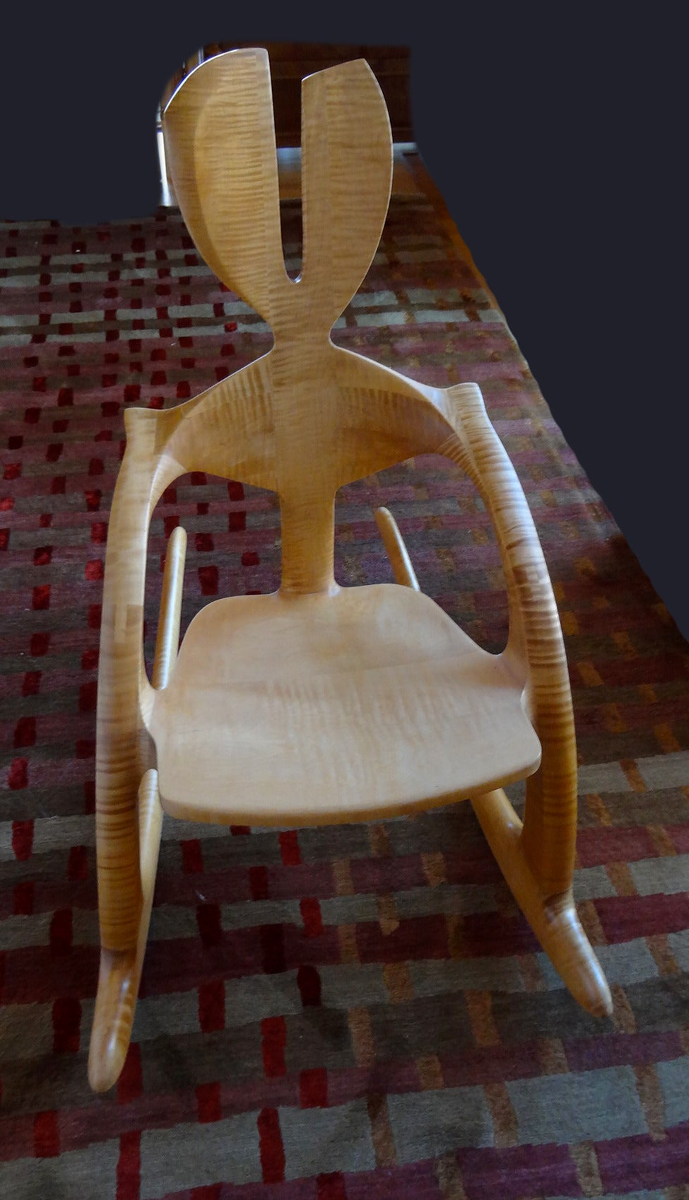 This Wendell Castle rocking chair is a unique variation on the Zephyr chair and is an excellent example of the artist's wit. The use of the beautifully figured solid tiger maple is also a rarity in Castle's seat furniture. The chair is constructed