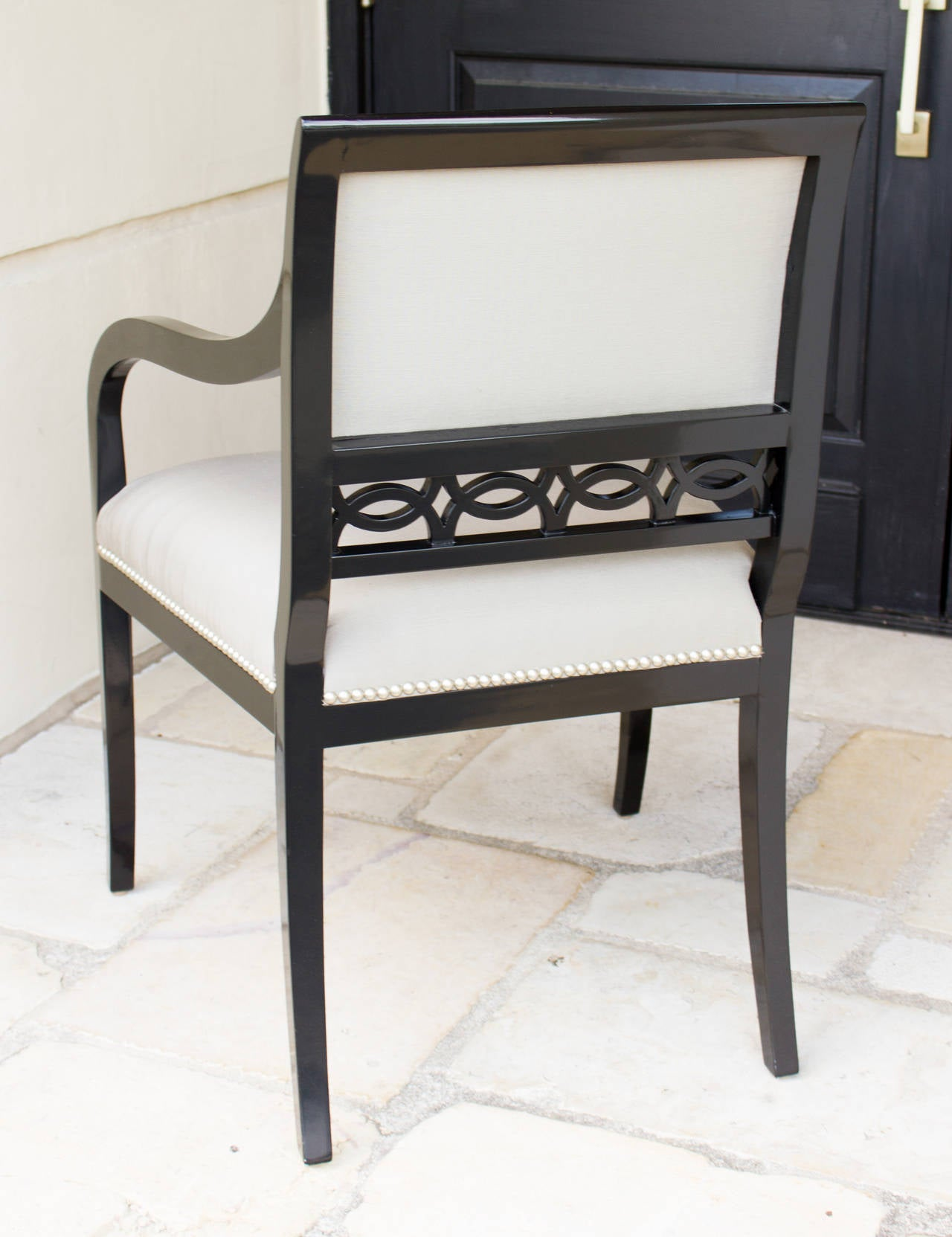 Black lacquer studded. A pair of studded Chandler armchairs from the Robert Brown Collection. The chair's frame is finished in black lacquer. Designed by Robert Brown in Atlanta, handcrafted in England.