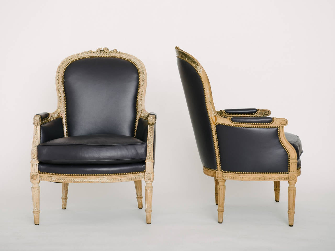 Pair 19th Century French Louis XVI style bergere chairs newly upholstered in blackberry lambskin leather.