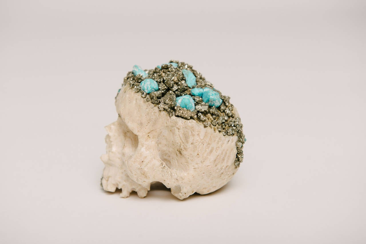 A modern momento mori hand-carved natural coral skull with pyrite capped tooth and exposed turquoise and pyrite Cap.