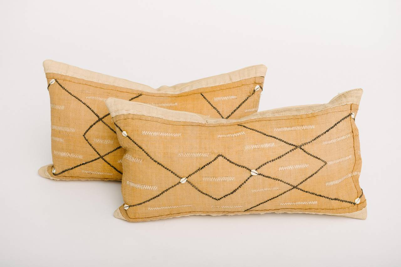 African shell and raffia Kuba woven textile throw pillows backed in buttery leather and are feather-down filled. Measures: 14 x 24.