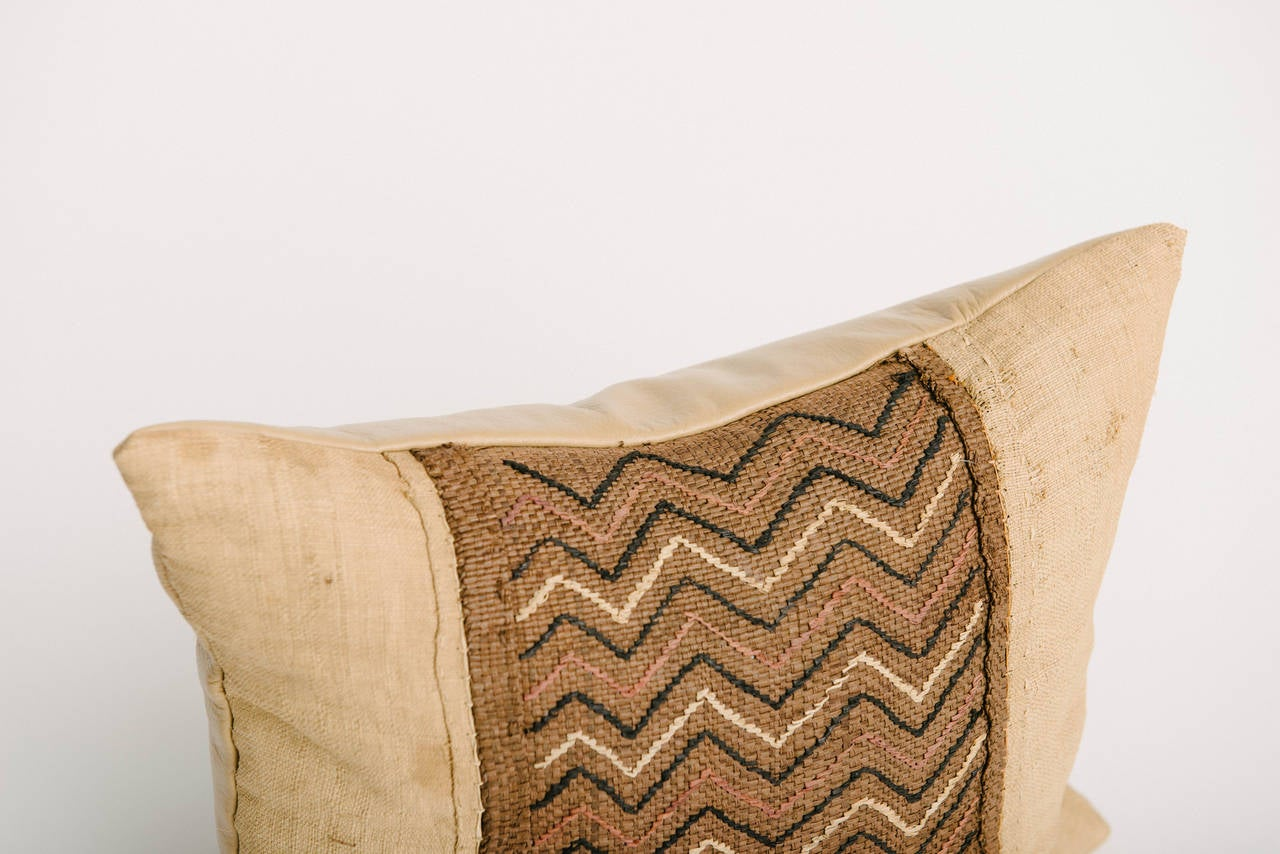 Vintage African raffia kuba woven textile throw pillow custom backed in buttery caramel leather and is feather down filled. Measures: 15 x 17.