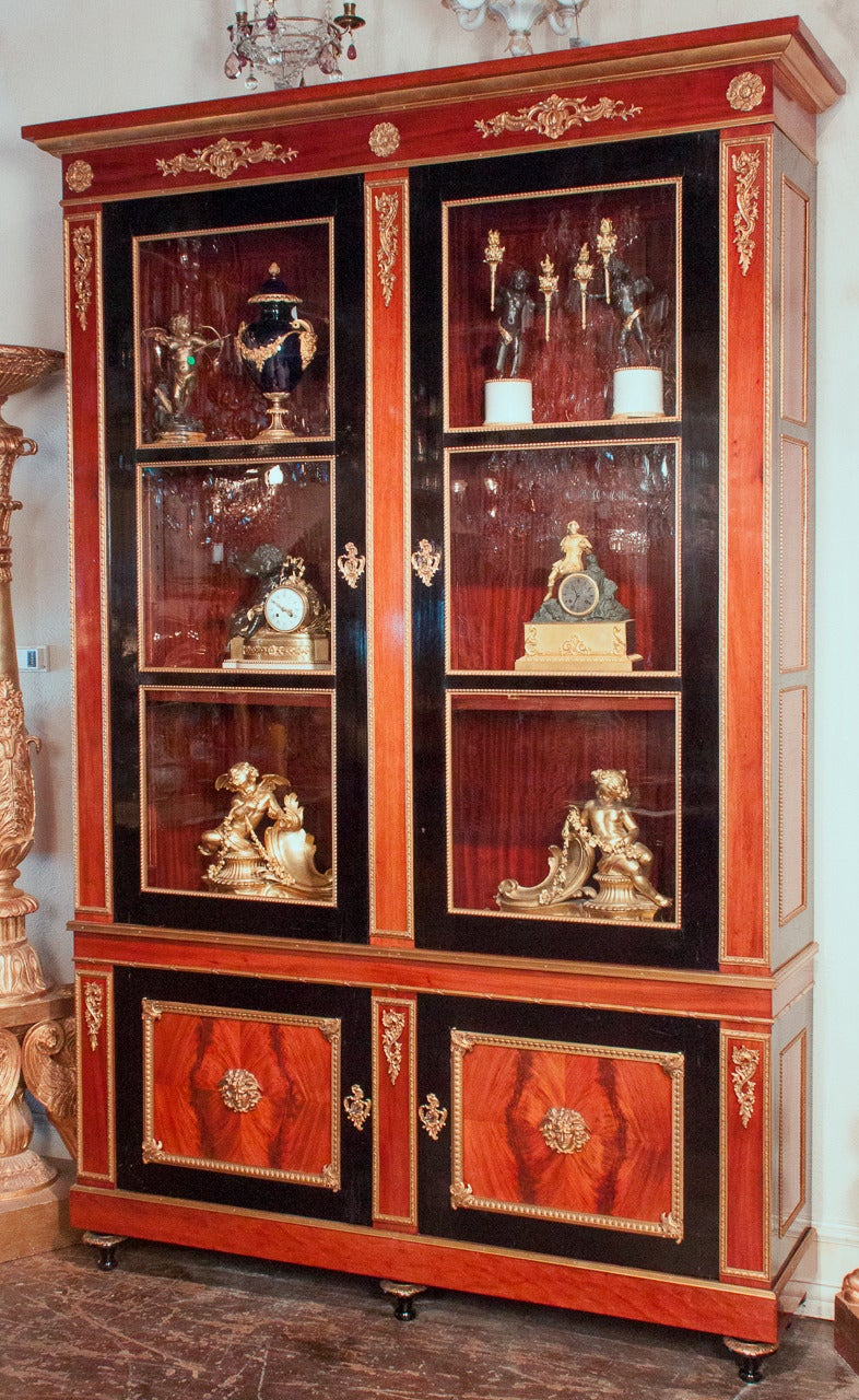Exceptional French Directoire style bookcase featuring impeccable gilt bronze detailing. Narrow sized bookcase composed of authentic French polished and black lacquered mahogany. Finely cast bronze mounts adorn the panels and lower cabinets. Having
