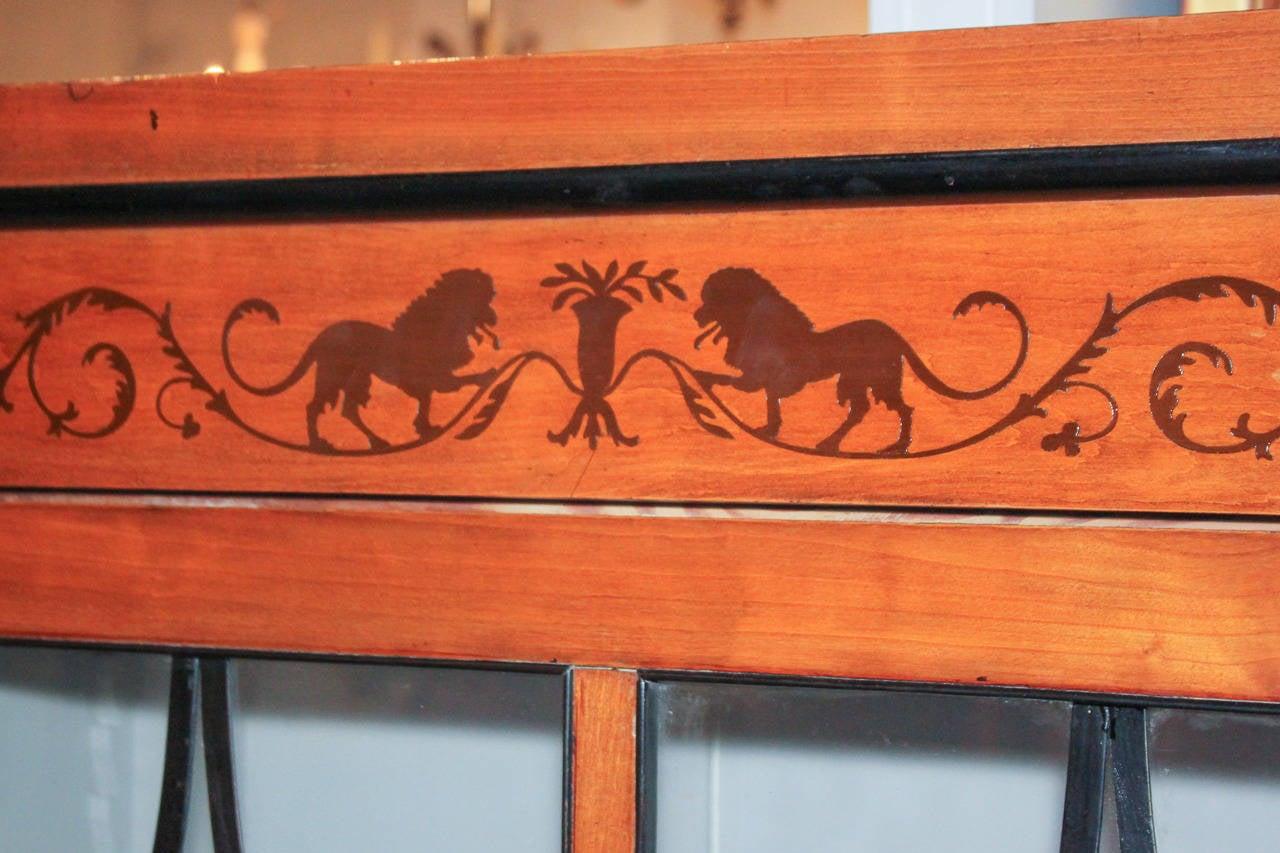 Sensational Biedermeier fruitwood and ebonized wood inlaid bookcase. Having intricate lion form and foliate inlays, ebonized accents, and wonderful finish.
