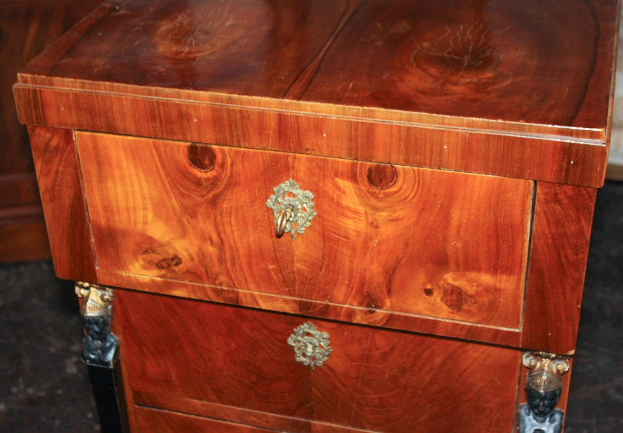 Splendid German Biedermeier mahogany and ebonized 4-drawer tall chest. Having ebonized and gilt figural caryatid head columnar supports, bronze mounts with quiver and bow motif, and a rich warm patina.
