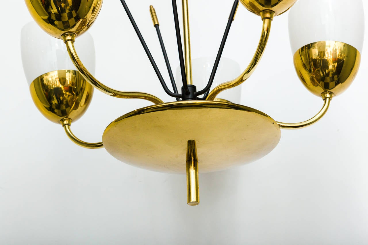 An elegant solid brass and milky glass five-arm chandelier in the manner of Paavo Tynell.