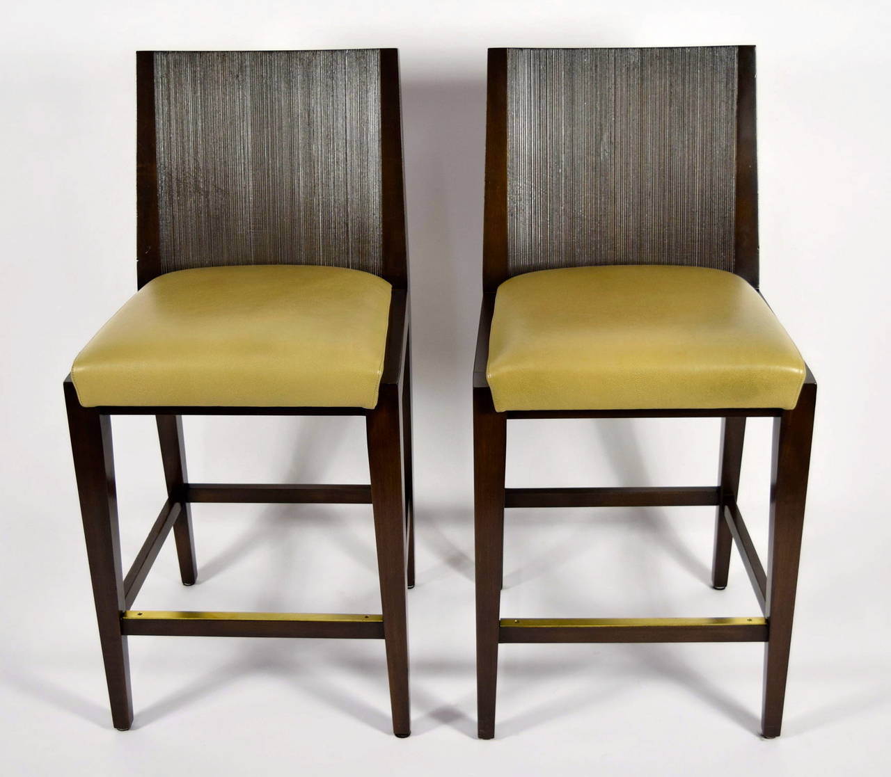 A beautiful pair of barstools by Axis. Kenya - tight seat with dark wood stained combed wood back, metal plate on footrest. Upholstered in great plains leather