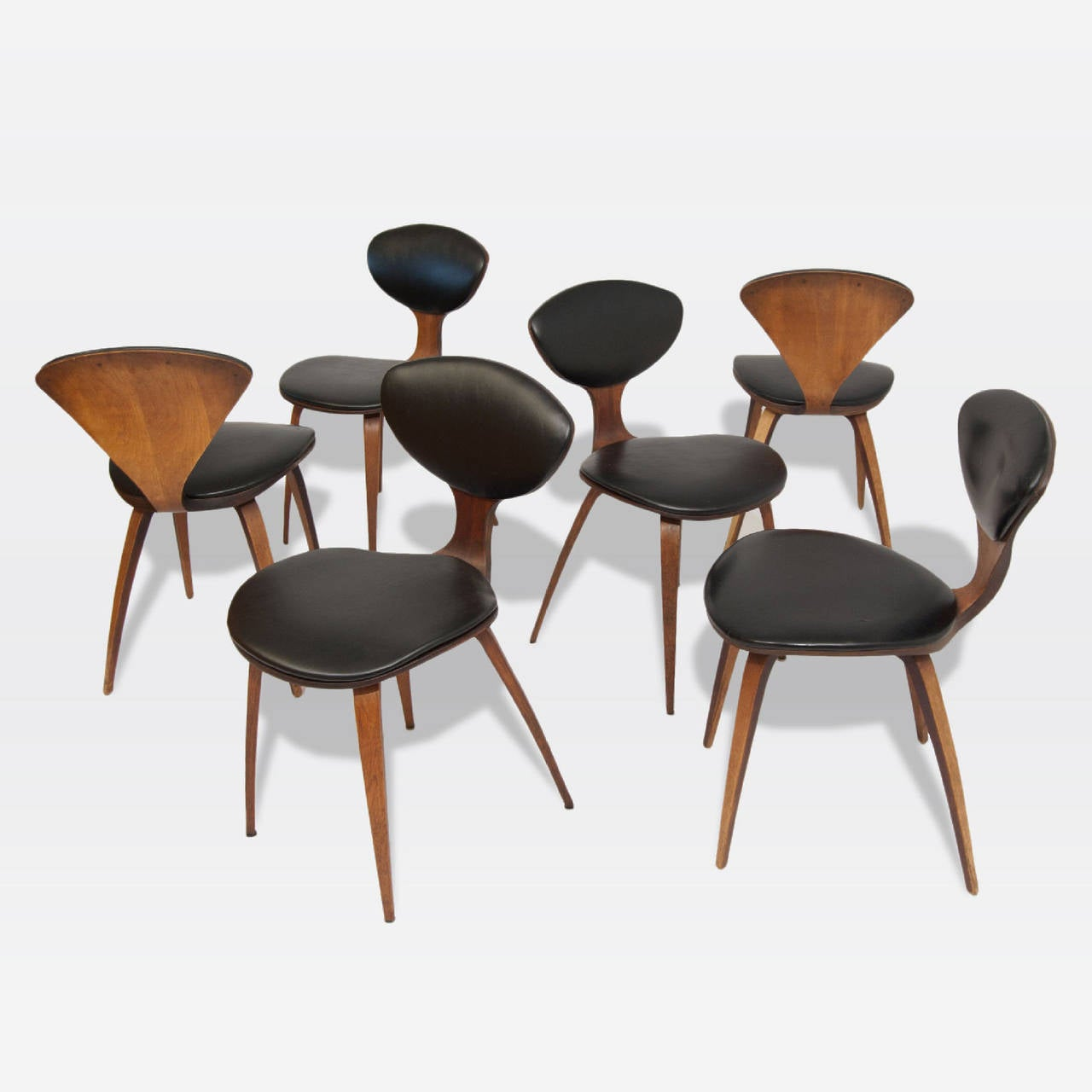 Set of six walnut side chairs with black vinyl upholstered seats. Designed by Norman Cherner, produced by Plycraft.