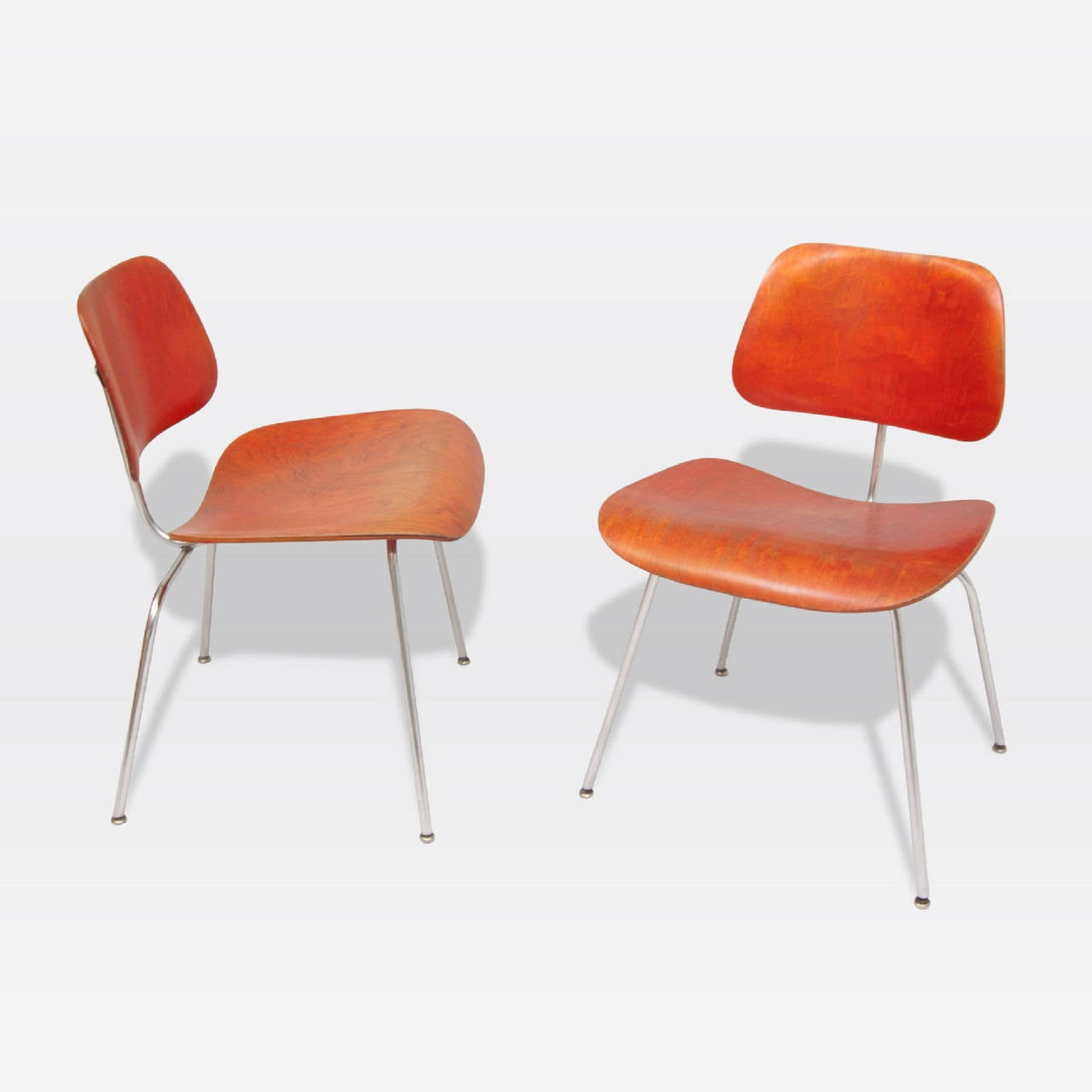 Pair of rare aniline dyed red ash DCM chairs with satin chrome frame. Designed by Ray & Charles Eames for Herman Miller.