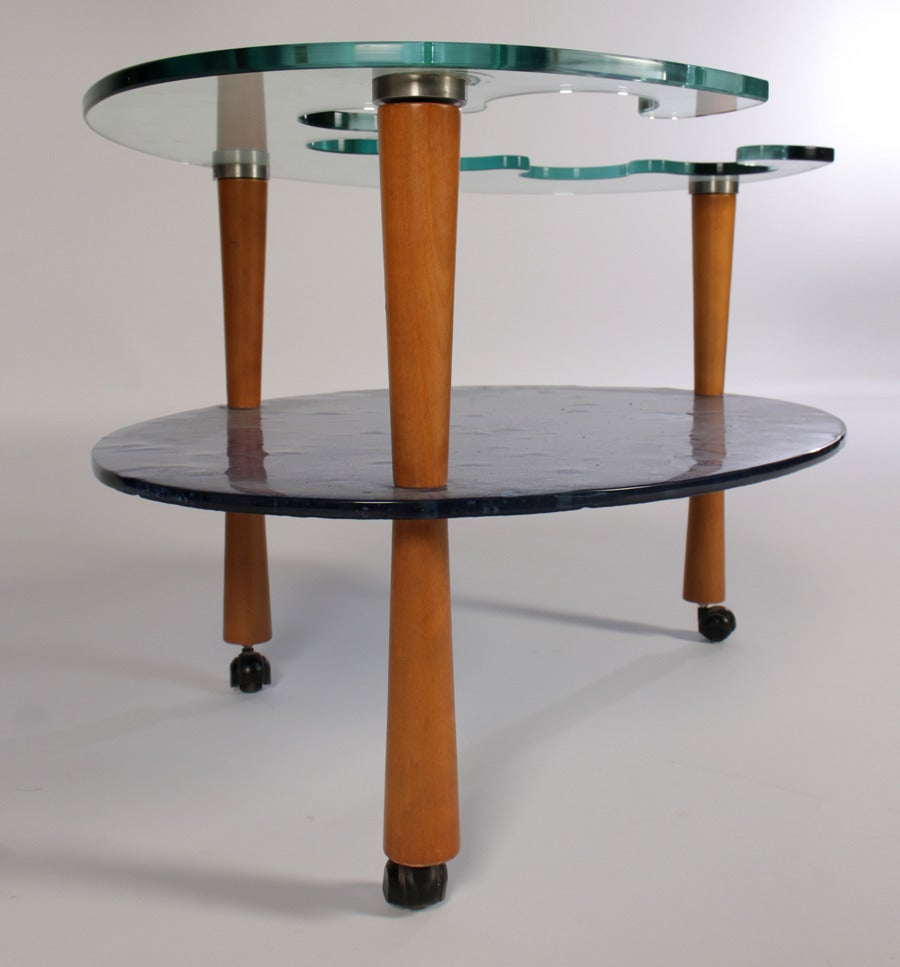 An Italian Mid-Century Modern glass bar cart having shaped glass top over blue cast glass lower tier shelf, all supported by wood tapered legs. 