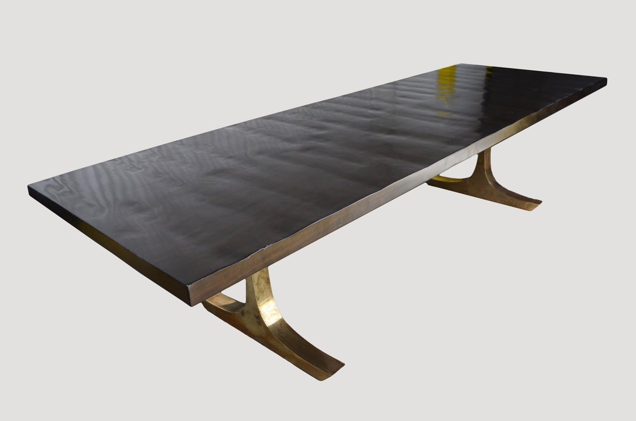 """Hand made dining table shown with """"C"""" style hammered bronze base. The cherry wood top has been hand finished with a french polish rather than left completely flat and stained espresso.  All slabs are hand selected. We only select the best. The Made"""