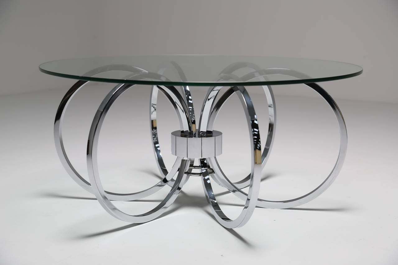 A Chrome Coffee Table Made From Series Of Rings And Glass Top
