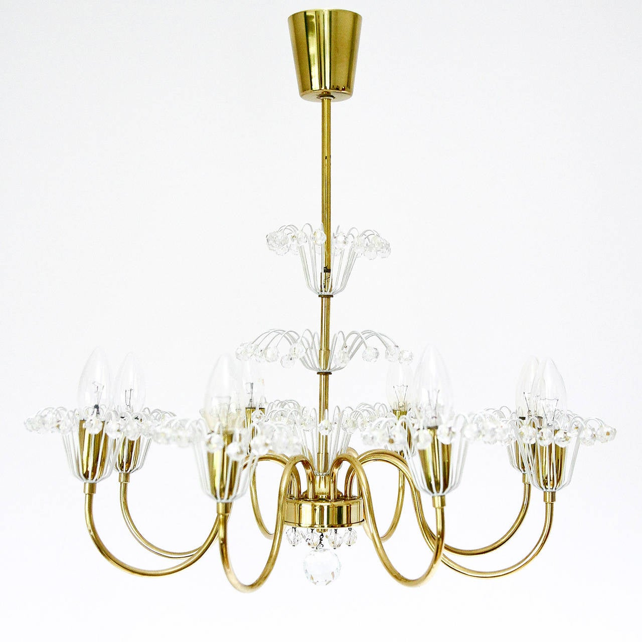 A very beautiful floral eight-arm chandelier designed by Emil Stejnar for Rupert Nikoll, Vienna Austria, manufactured in Mid-Century, circa 1950.  It is made of brass and many small cut crystal glass crystal. The light has eight sockets for E14