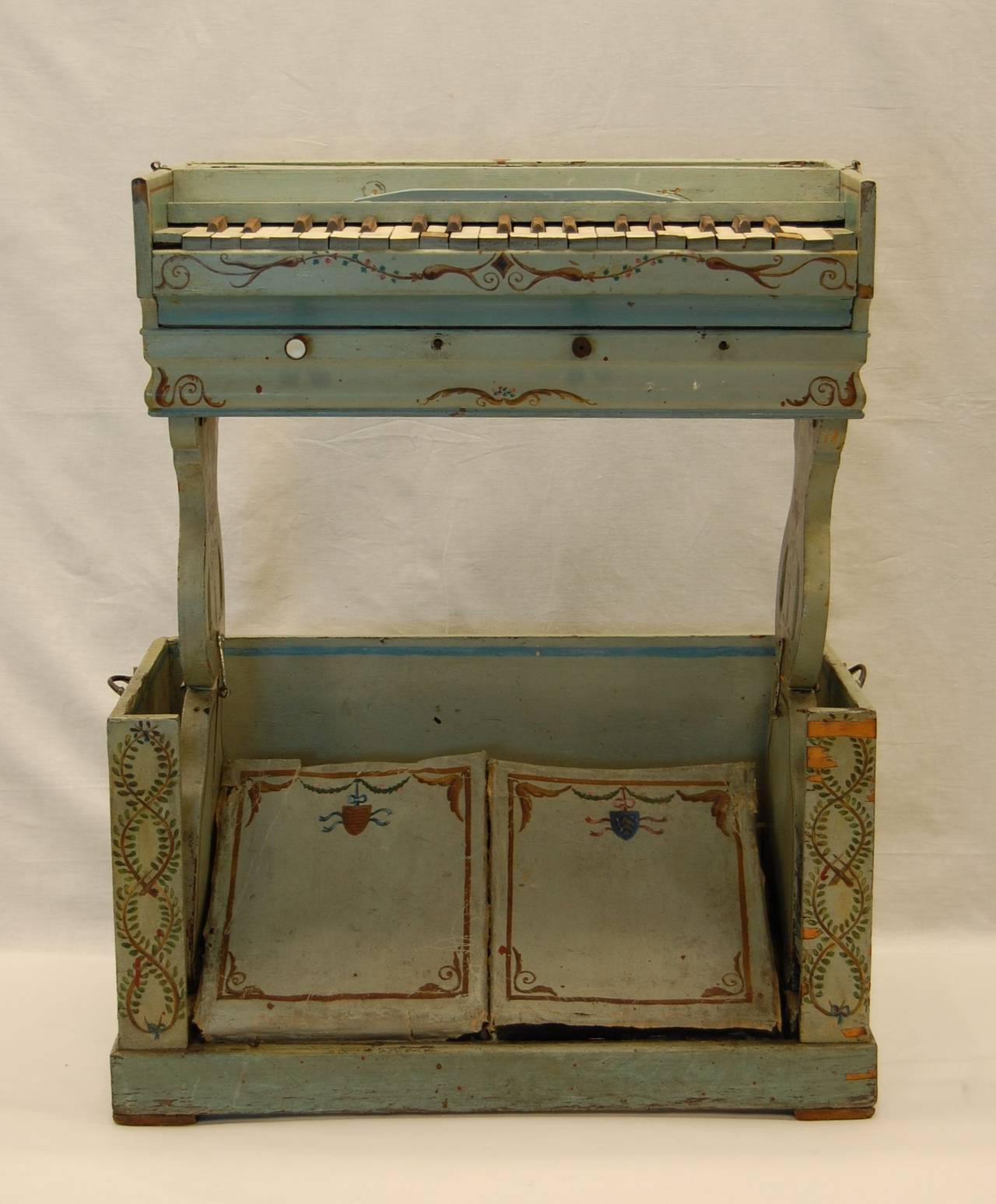 Child's organ with two peddles which force air upward through internal passages in each upright support. Needs restoration (please see condition notes below). Beautifully painted and decorated. This unit folds down into itself, dimensions in folded