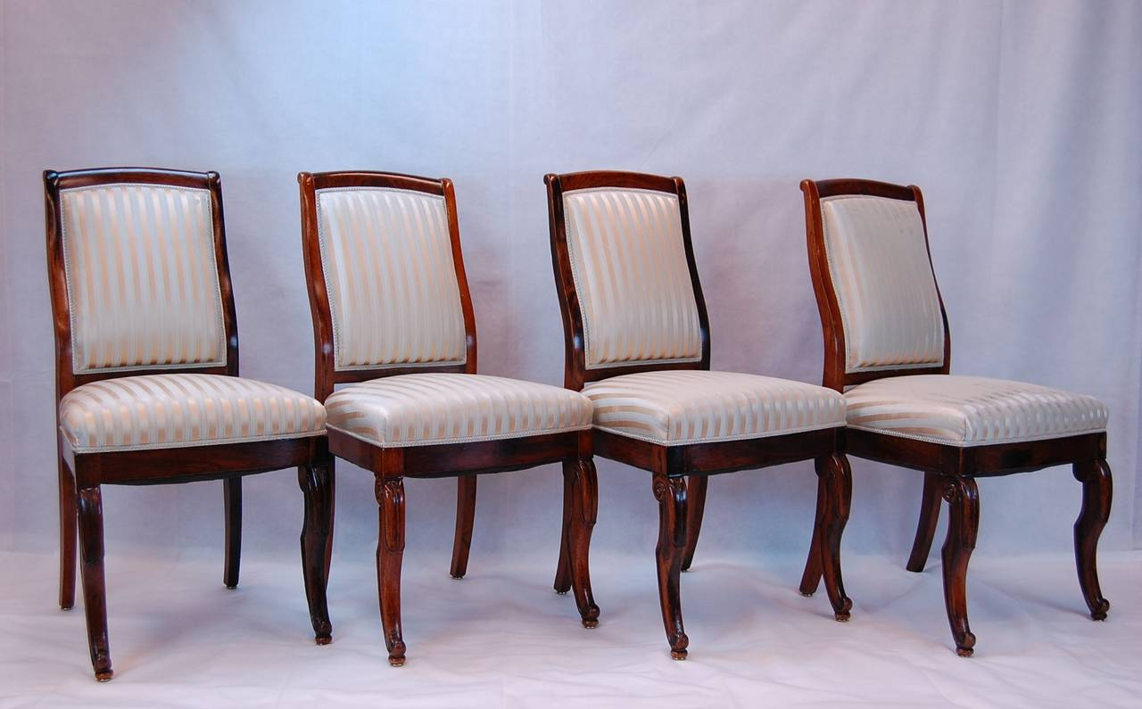 Set of four matching 19th century French rosewood side chairs with carved front legs and saber back legs. Excellent, tight frames, need only to be recovered.