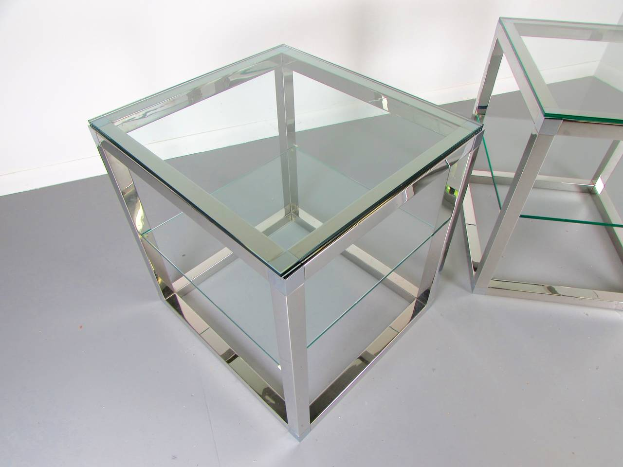 Minimalist Chrome Cube Tables With Glass Shelves In The