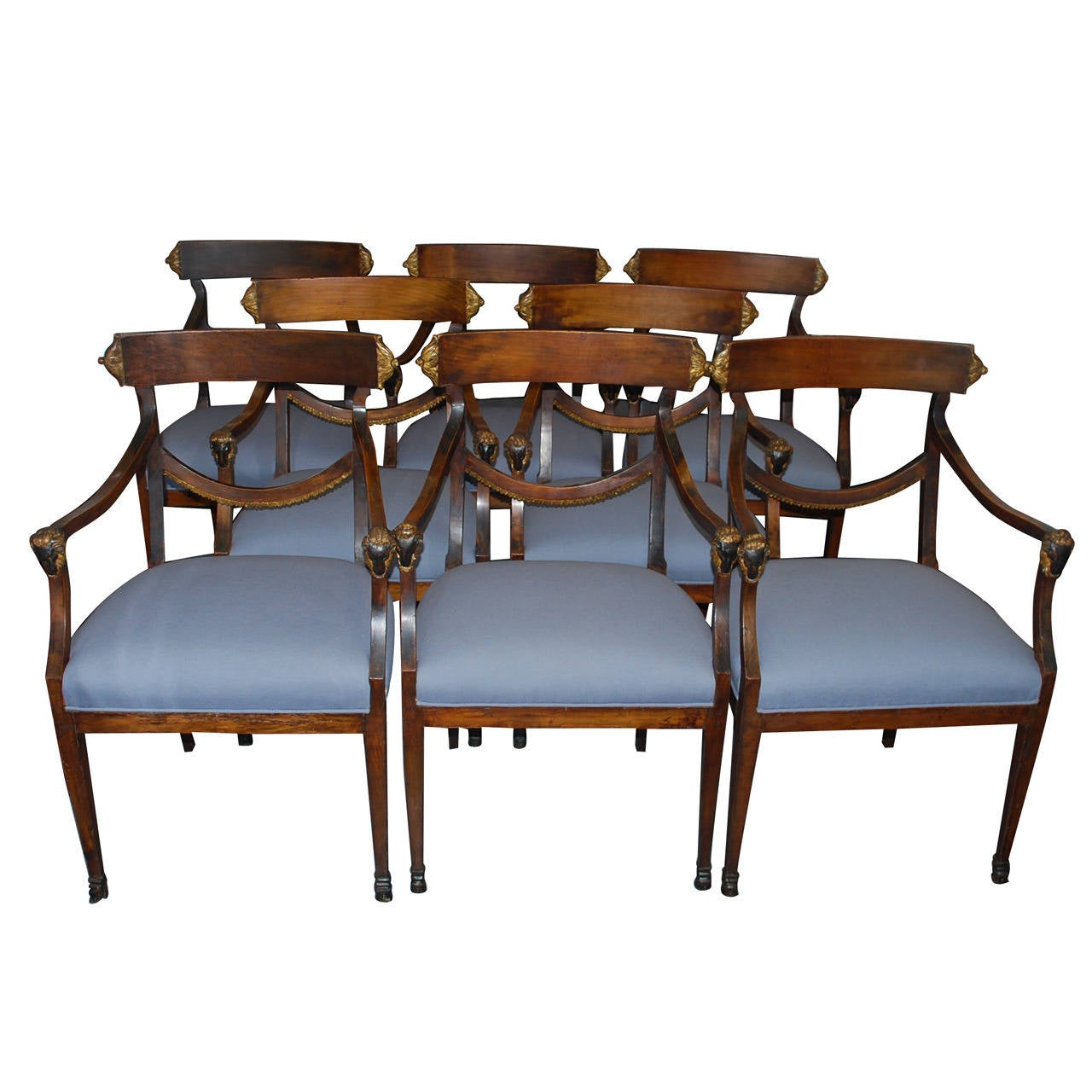 Set of eight Italian Neoclassical ram's head dining chairs.  Eight neoclassical parcel-gilt and parcel ebonized wood armchairs with ram's head armrest terminals and front hoof feet, Italy, circa 1800. Provenance: Estate of Louis Auchincloss Newly