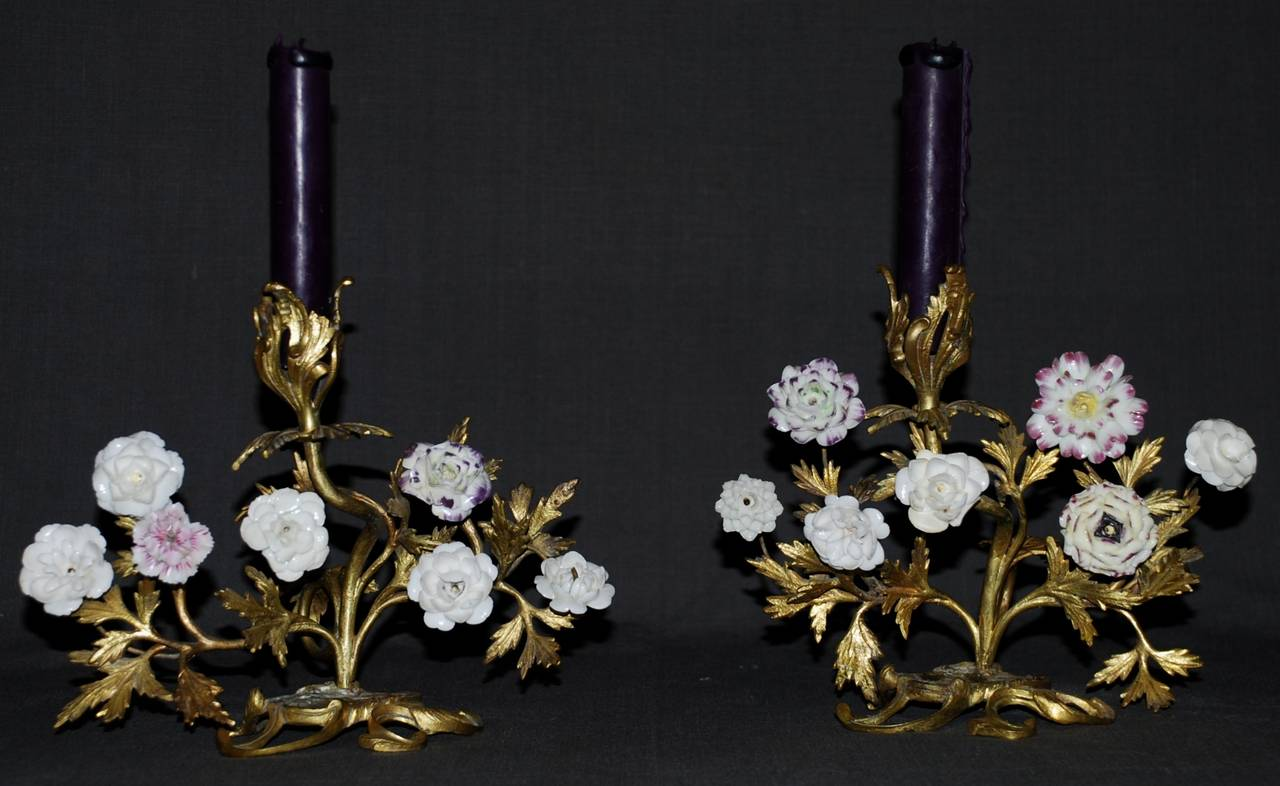 Pair of Louis XV ormolu candlesticks with porcelain flowers.  Elegant tulip-form candle nozzles and varied puce and white and period soft paste porcelain flowers. France, mid 18th century. Dimension: 9