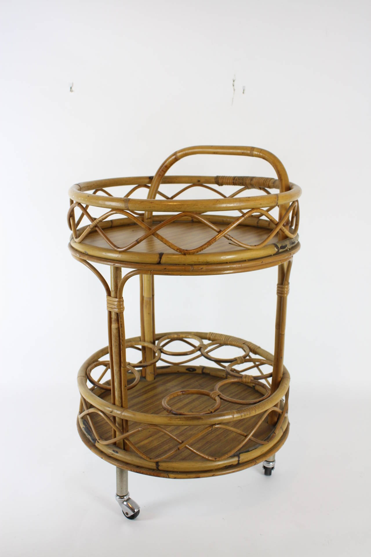 Spanish bar cart in Mediterranean style. It has two shelves; each shelve has a melamine base and the structure of the bar cart is made of bamboo and wicker.