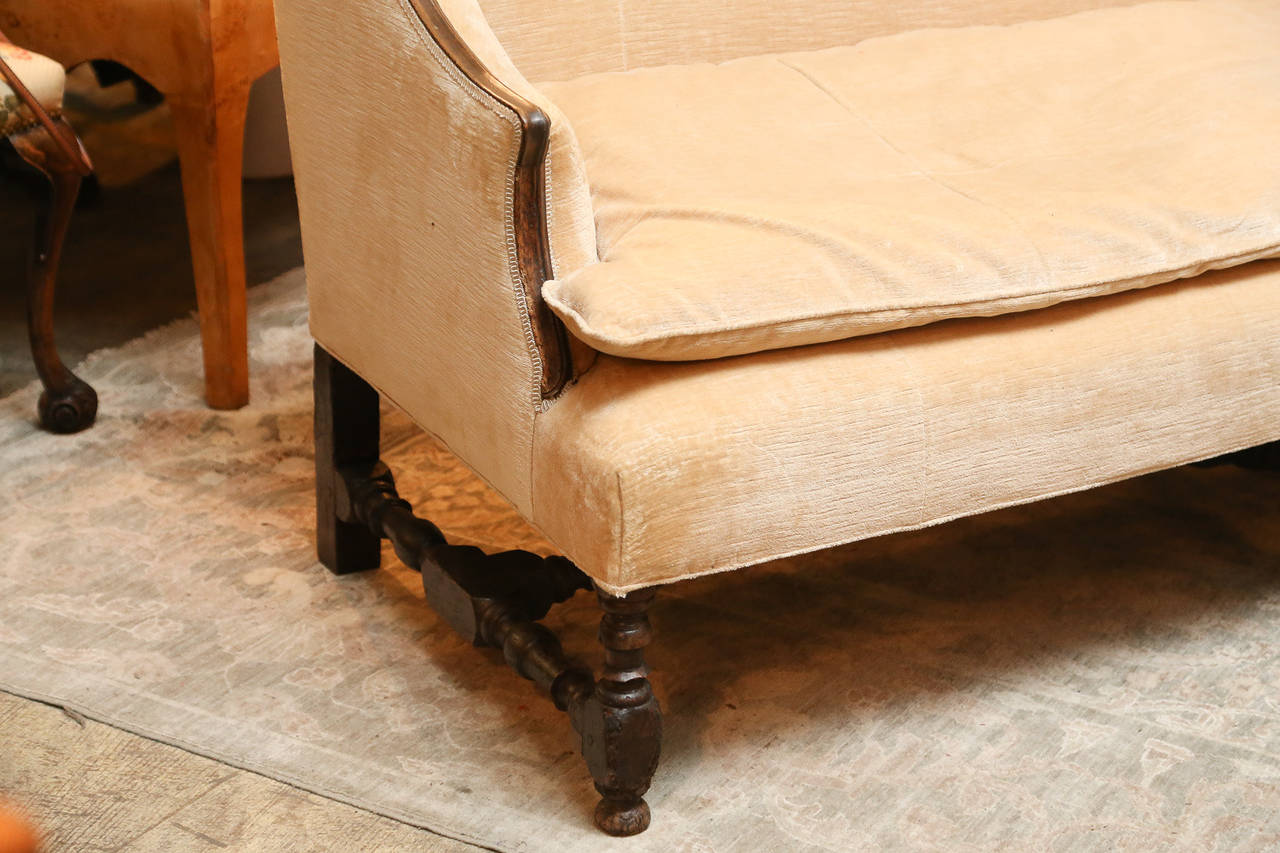 French settee back with shaped back and semi-wing sides.  Oak frame exposed around upholstery.   Legs and stretcher are turned oak.