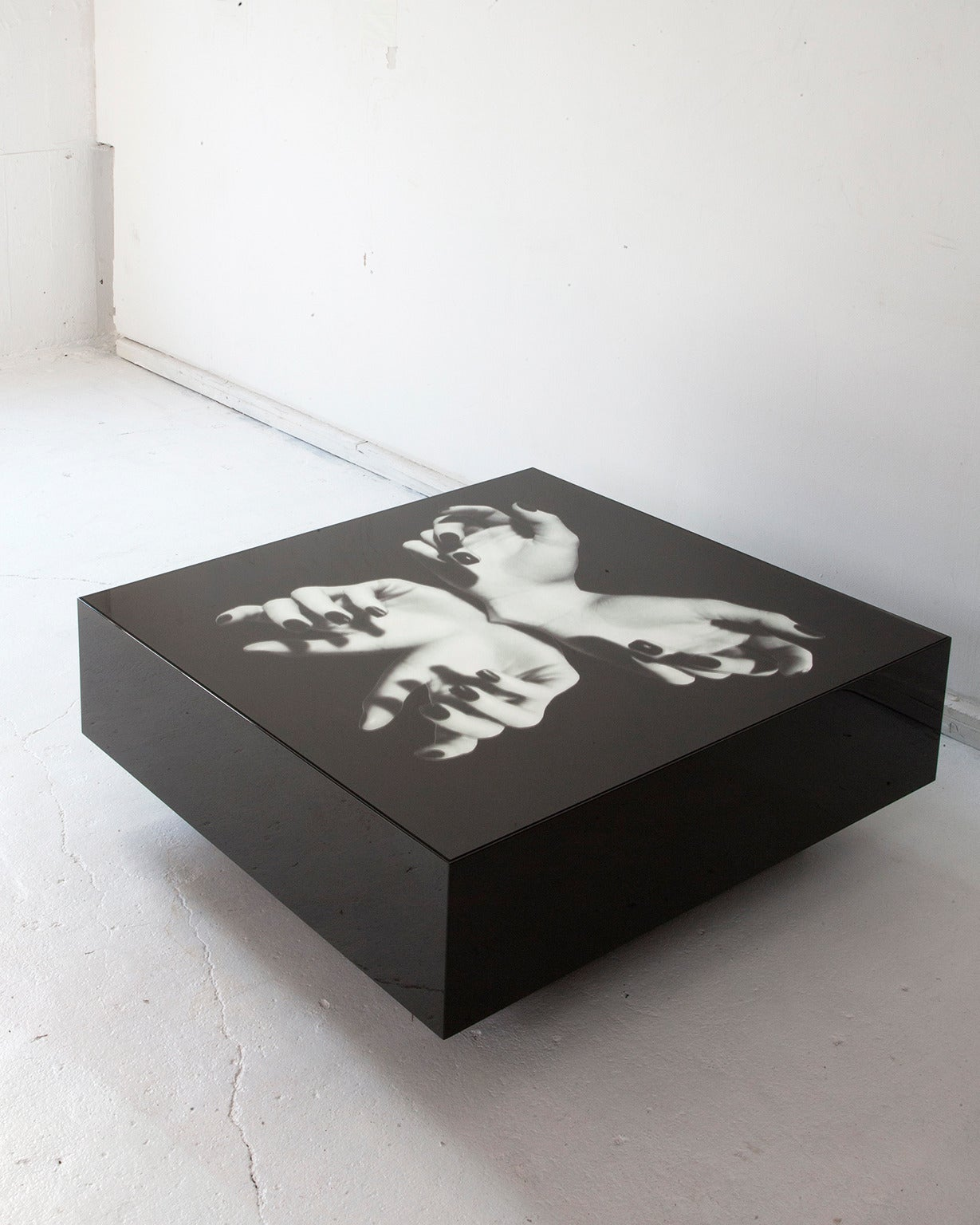 Cocktail table with black mirror top printed with an original digital collage by artist Gordon Magnin.  Shown in black. Measures: 36