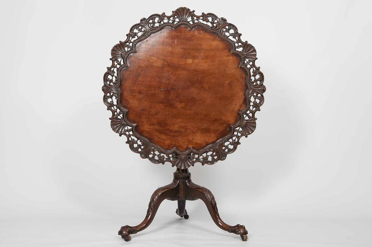 Early 19th century George III mahogany occasional table with tip-up top, ornate foliate and shell carved top on baluster turned column, leading to carved hipped tripod with claw and ball feet.