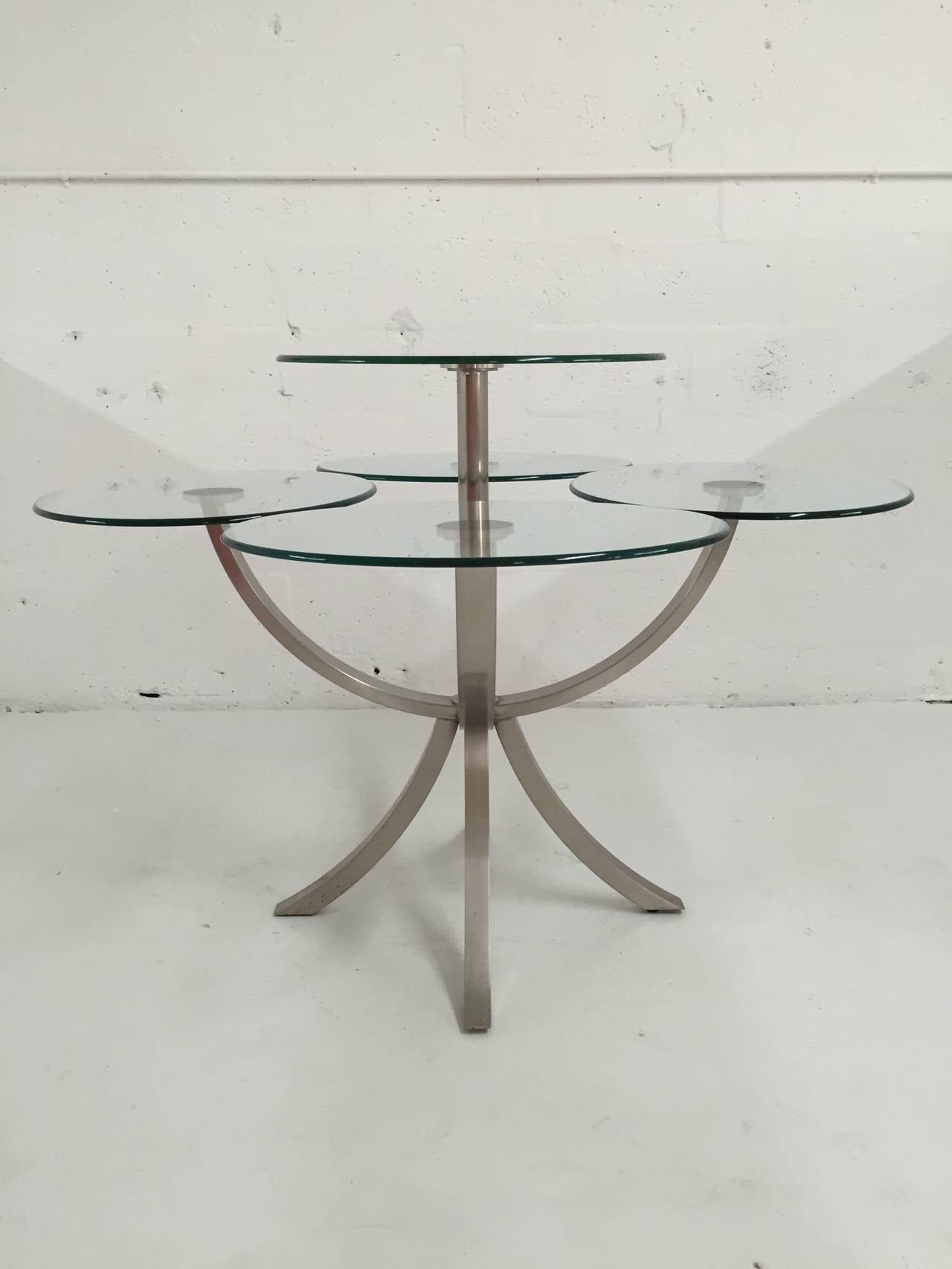 Brushed steel and glass dining table by DIA, Design Institute of America with four individual oblong glass place settings and an elevated round glass serving shelf.  Additional Measurements: 24'' - width of place setting. 20