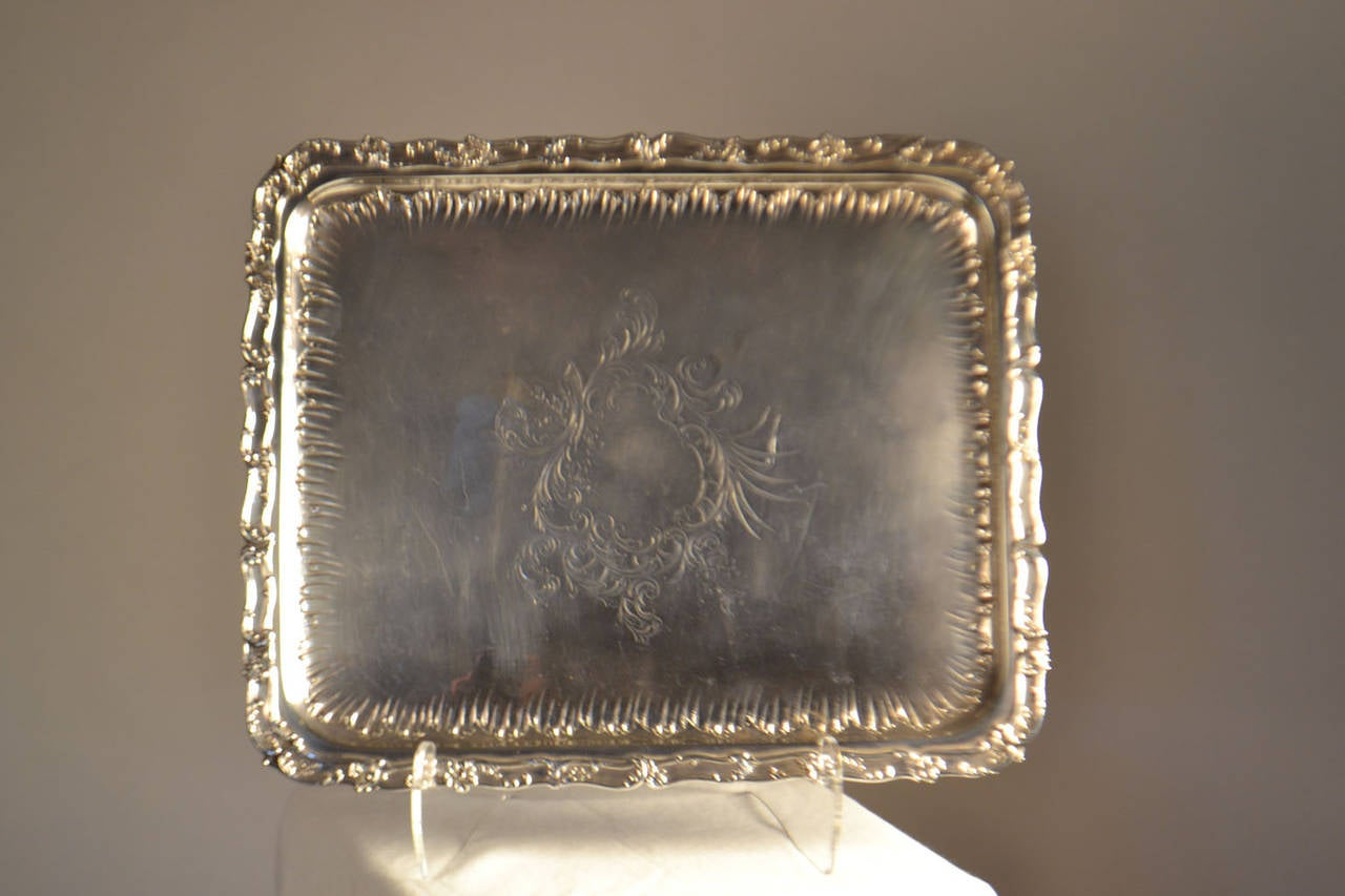 Gorgeous sterling silver tray with interior gadrooned border and centralcartouche and floral motif.