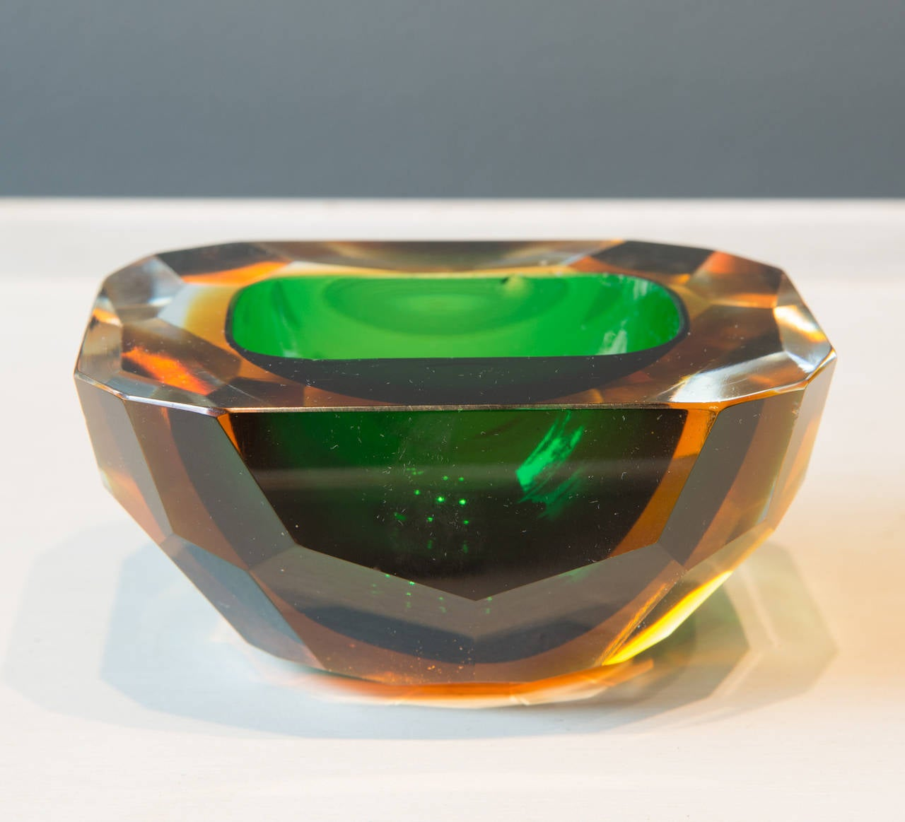 Lovely faceted very heavy crystal bowl with emerald green color, 20th century.  Also available is a companion bowl with a sapphire blue color interior.