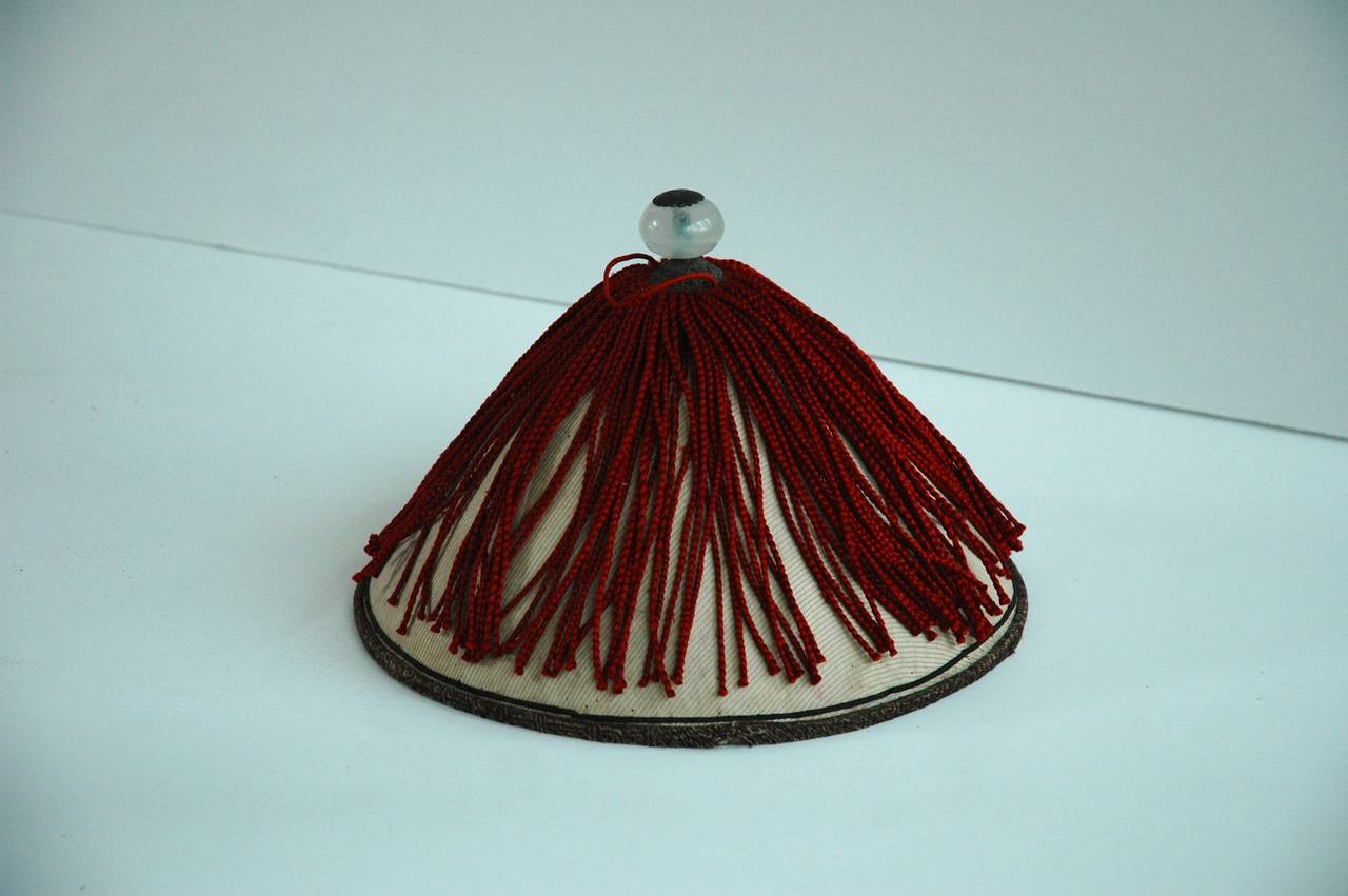 A Chinese mandarin summer hat with red silk tassel trim and glass finial top. Includes antique Chinese leather hat box.