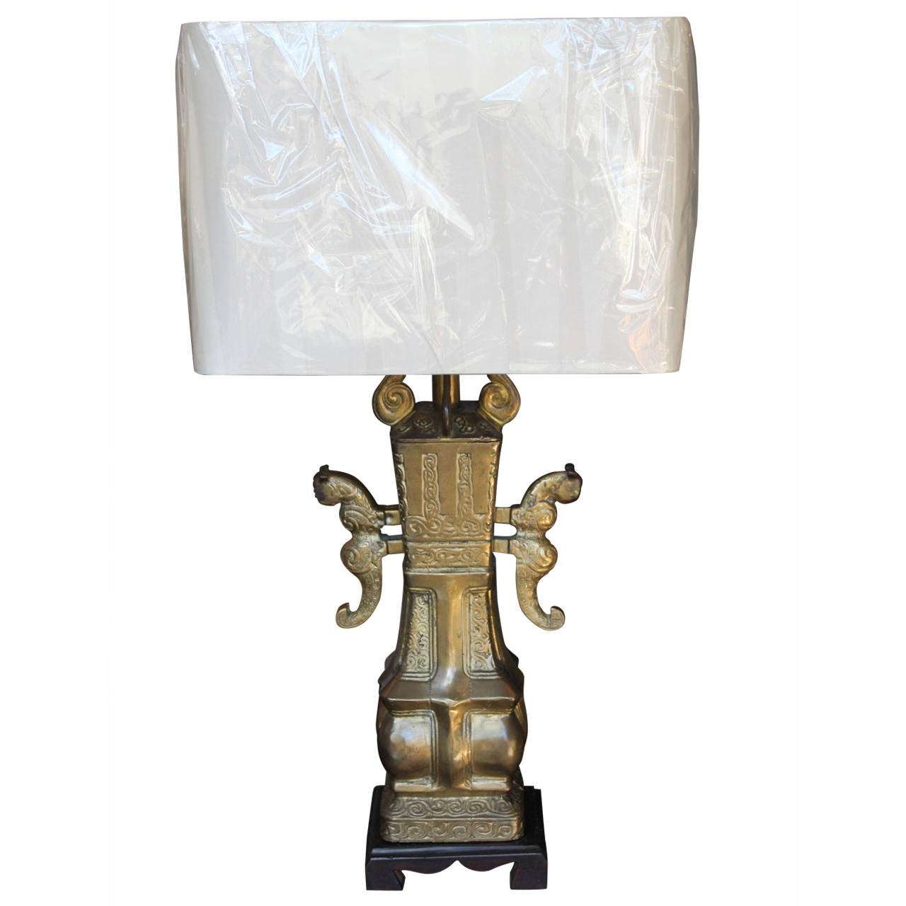 Very heavy bronze lamp in the style of Marbro with an Asian base and figured handles. The lamp has a nice patina and includes a modern, new silk shade, circa 1970.