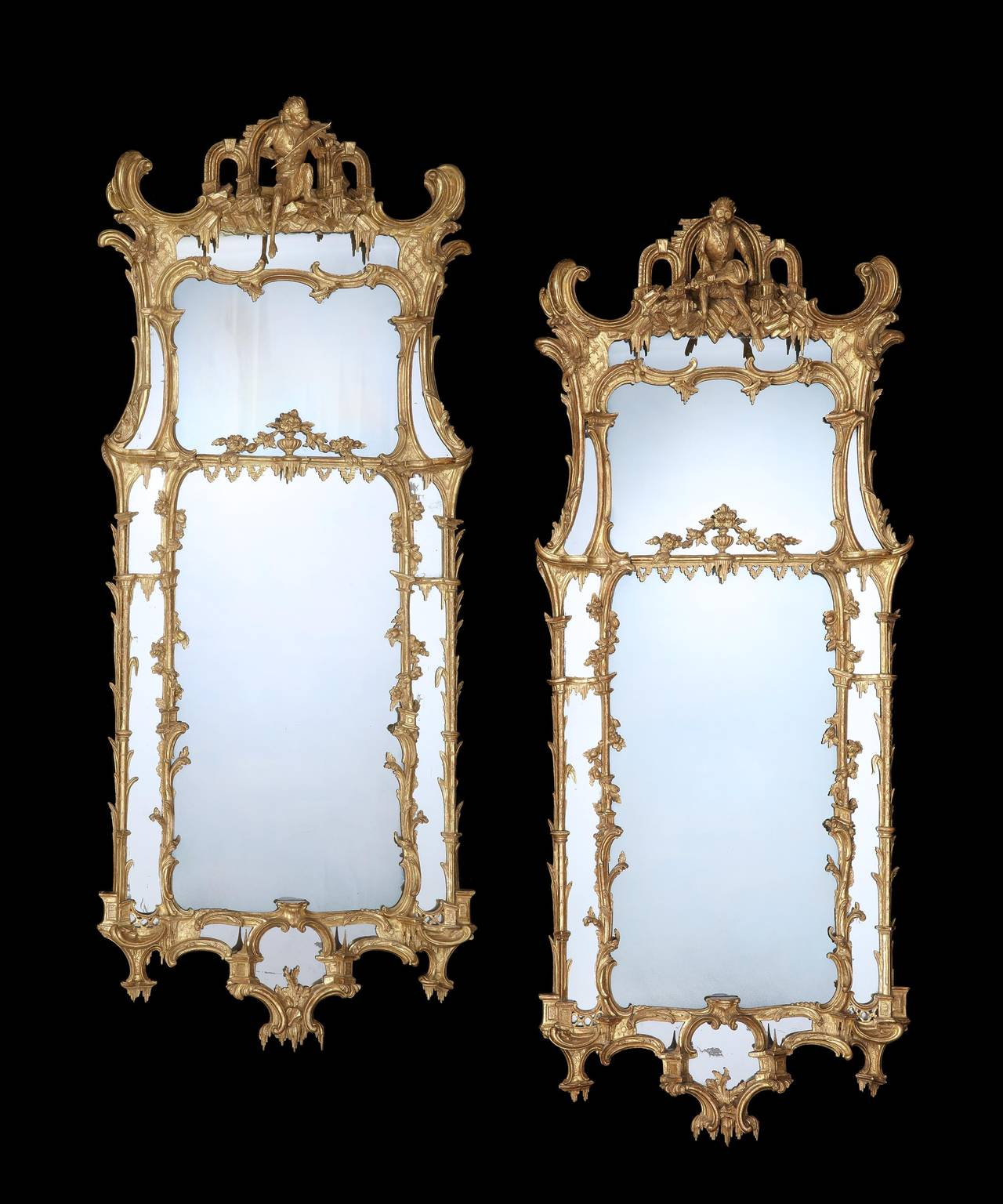 A Pair of George II carved gilt-wood Pier Glasses in the manner of Matthias Lock. This pair of mirrors encapsulates the highly imaginative fanciful design of the french picturesque that prevailed in the mid-18th century with the nautilistic palm