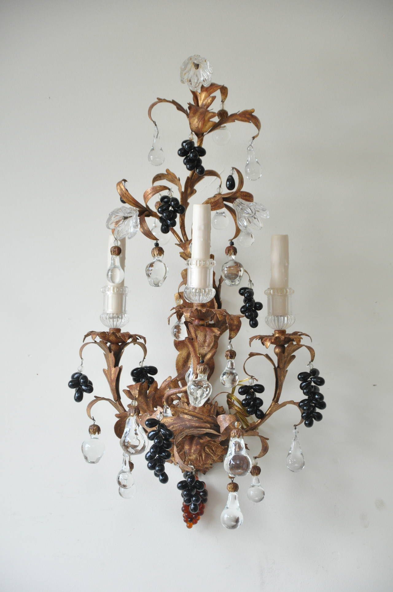 Stunning pair of 19th century gilt metal and crystal sconces. Sold by Paul Ferrante (Los Angeles, CA).   Each four-light sconce (three vertical/ one concealed horizontal) is adorned with a combination of hanging crystal flowers and fruit, colored