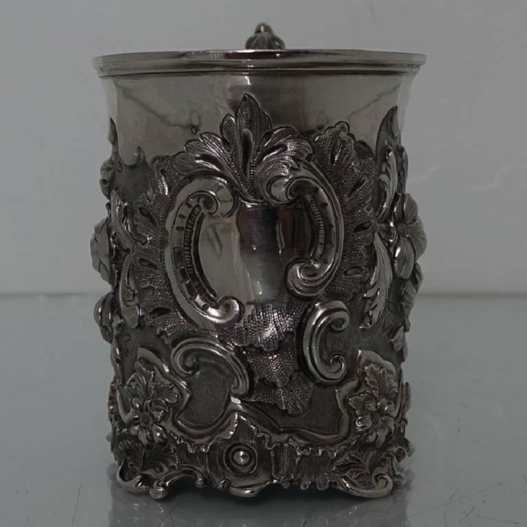A truly elegant early Victorian christening mug, beautifully floral chased throughout which is set on a matted background for highlights, the centre front and behind the handle have elegantly shaped cartouches. The handle is scroll formed and