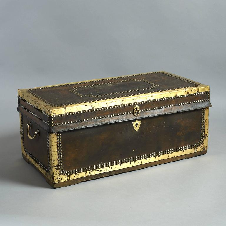 A good early 19th century leather travelling trunk, with panelled brass studding and having two carrying handles, lined with camphor wood and retaining an early retailer's label for Charles Hawkins, 86, Strand, London.