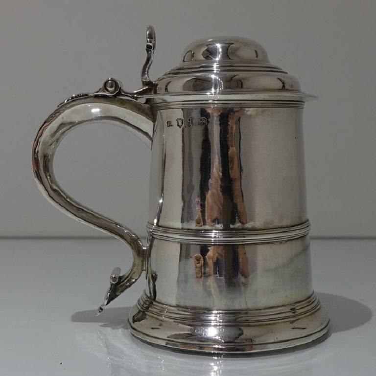 A beautiful tapered cylindrical tankard and cover with domed hinged lid and scroll handle. The tankard has a lower applied wire to the body for highlights and an elegant lower skirt for lowlights. The lid is hinged with a stylish cast thumbpiece and