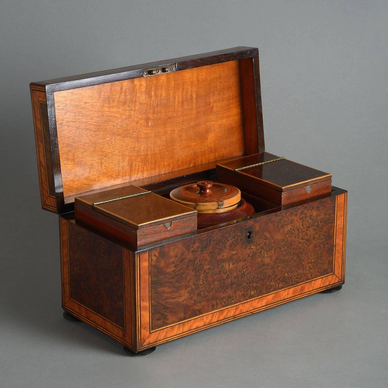 A George III Period burr elm and satinwood veneered tea caddy, retaining its original compartments and mixing bowl.