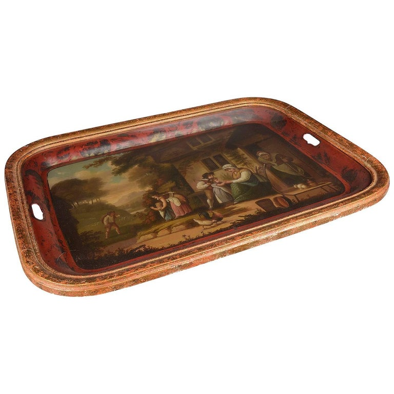 A very pleasing 19th century English red painted tole tray, having a rural family scene out side an old farm house painted to the centre, a red boarder and set in a gilded frame with glass to protect it. We can have faux bamboo bases made to turn