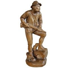 Kleine geschnitzte Skulptur eines Jägers mit Gewehr und Hund