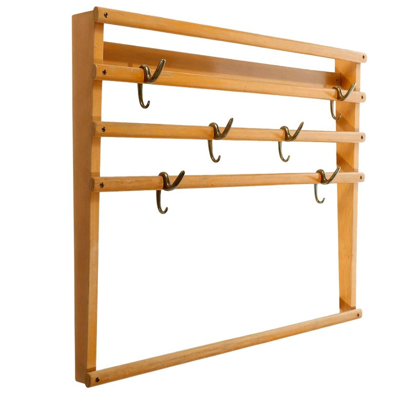 A wardrobe by Carl Auböck, Vienna, Austria, manufactured in midcentury, circa 1950. It is made of a beech wood frame in an aged and very warm tone. There are six patinated brass hooks (similar to bronze) which can be positioned randomly on the
