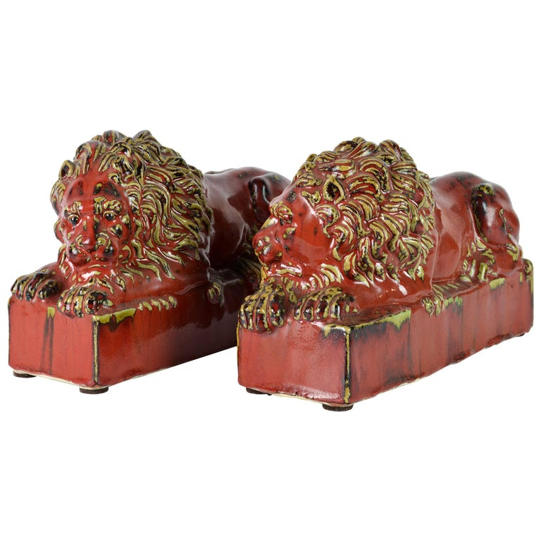 Opposing Pair of 20th Century Oxblood and Celadon Glazed Ceramic Resting Lions For Sale