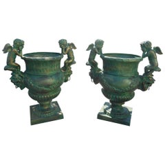 Amazing Pair of Cast Iron Urns with Cherubs on the Sides