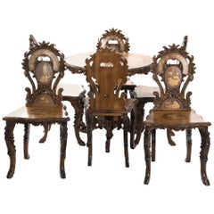Swiss Black Forest Carved Marquetry Tilt-Top Table and Six Chairs