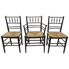 William Morris, Five Ebonized Rush Seat Sussex Side Chairs and Matching Armchair